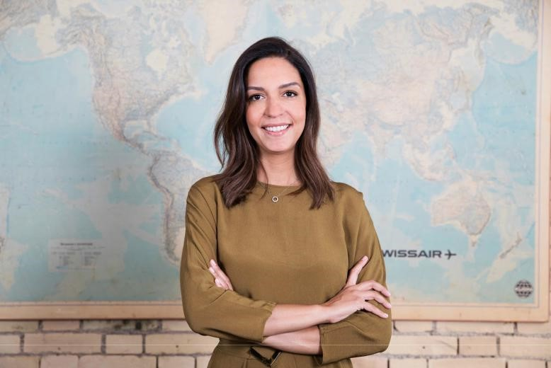 Fernanda Barrence Mutz, CEO & Co-founder of The Trip Boutique standing in front of world map
